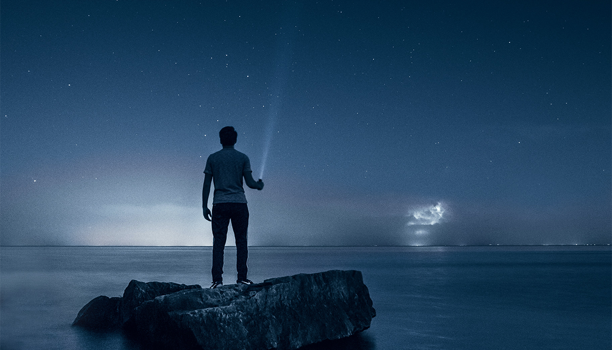 Man stands on a rock. He is looking across the blue sky.