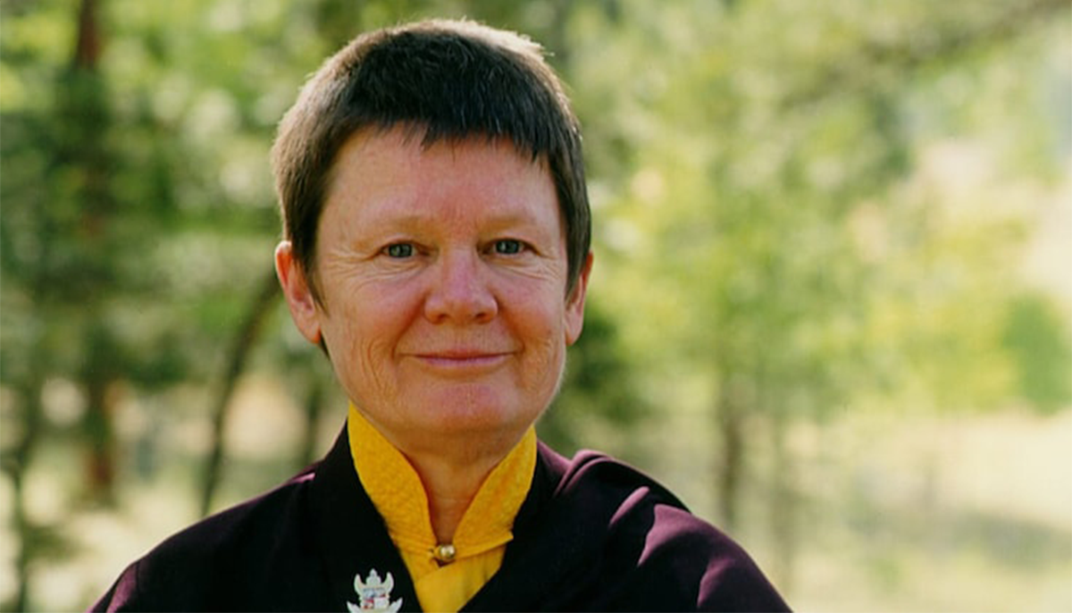 Pema Chodron smiling at the camera. She is wearing maroon robes overtop of a yellow shirt. There are trees in the background.