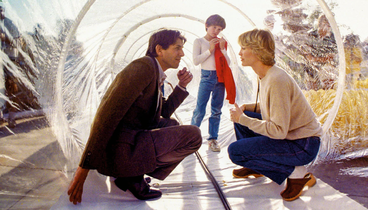 Three people in a plastic tube. A man and woman are crouched and looking at each other and there is a young boy behind them.