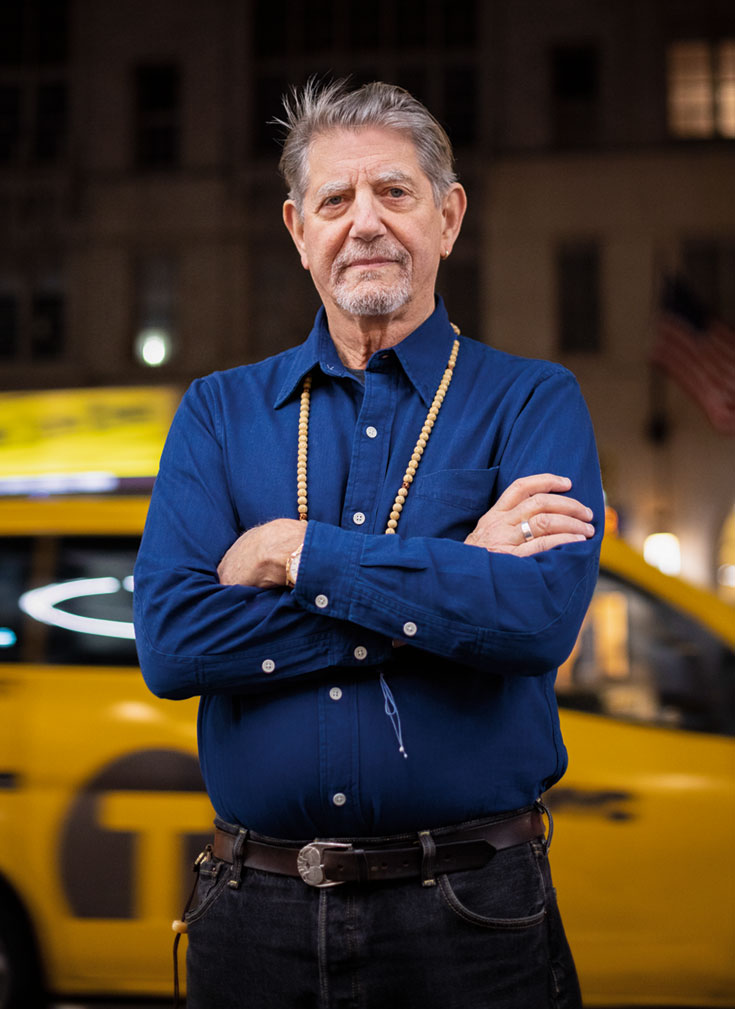 A man standing with his arms crossed in front of a taxi. He is wearing a blue long-sleeve shirt and black pants.