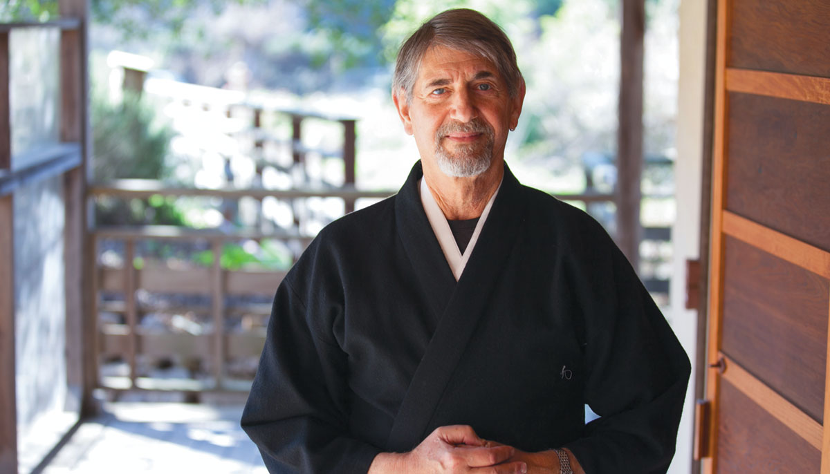 A man smiles and stands in black robes.