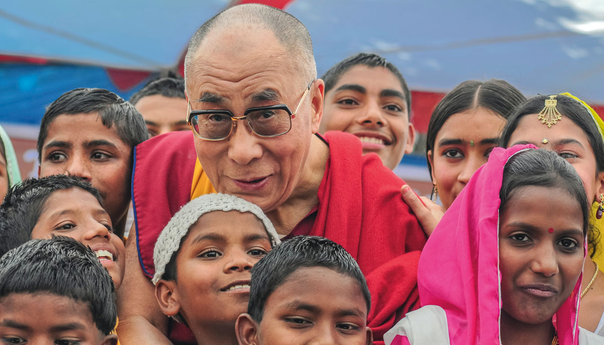 The Dalai Lama with a crowd of children. They are all smiling.