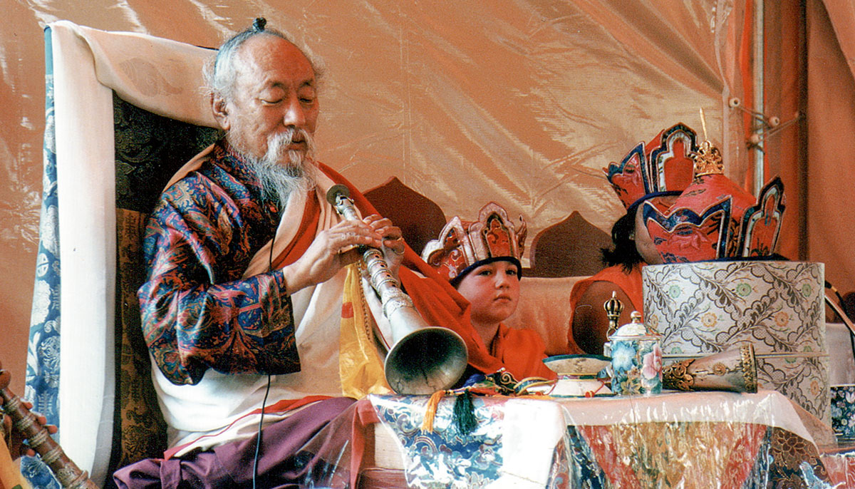 A man with a horn. Children are sitting next to him.
