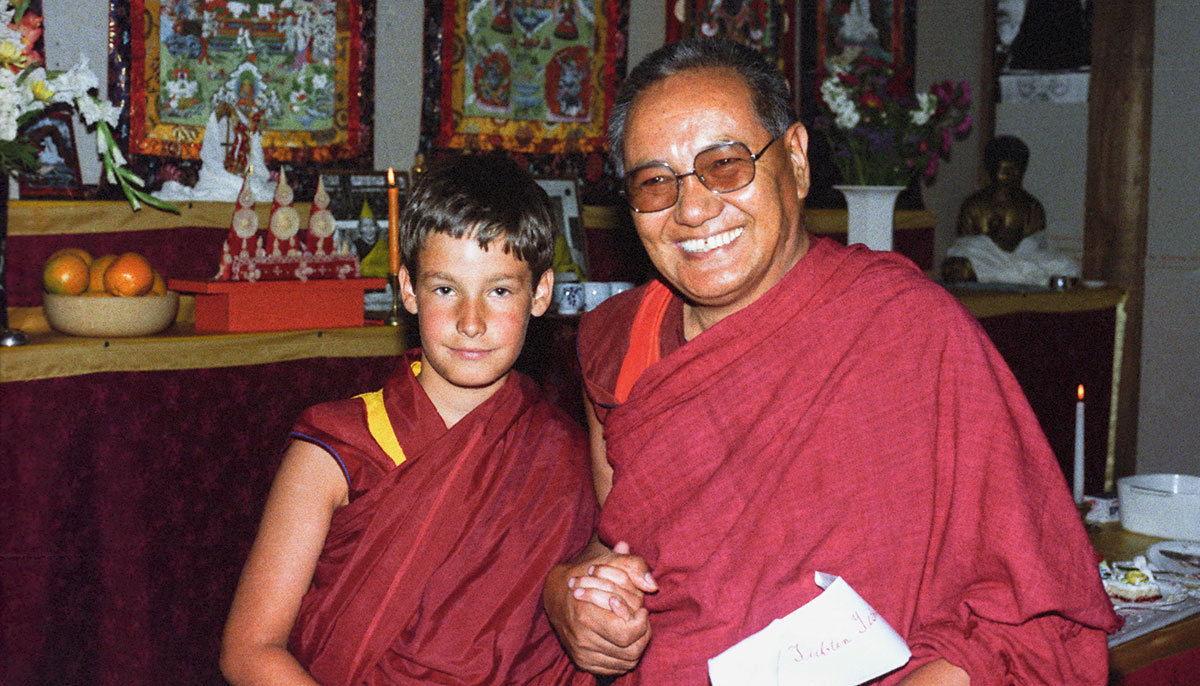 A young boy in monk's robes next to an older man with glasses in monk robes.