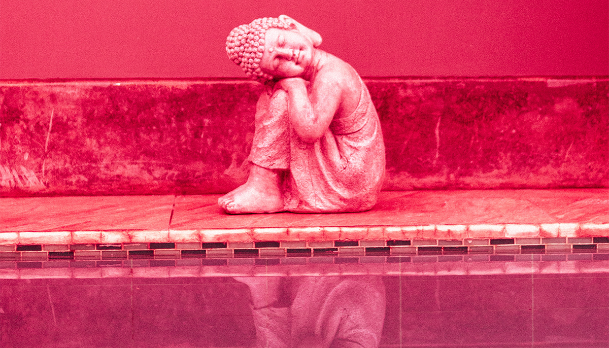 Statue on the edge of a pool. It is curled into itself, and the photo is overlayed in red lighting.