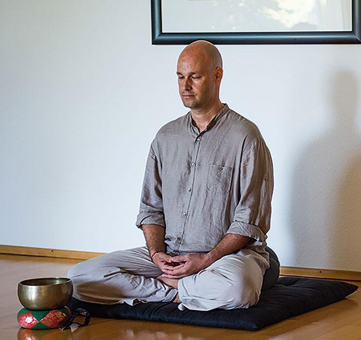 A man wearing grey clothes meditating.