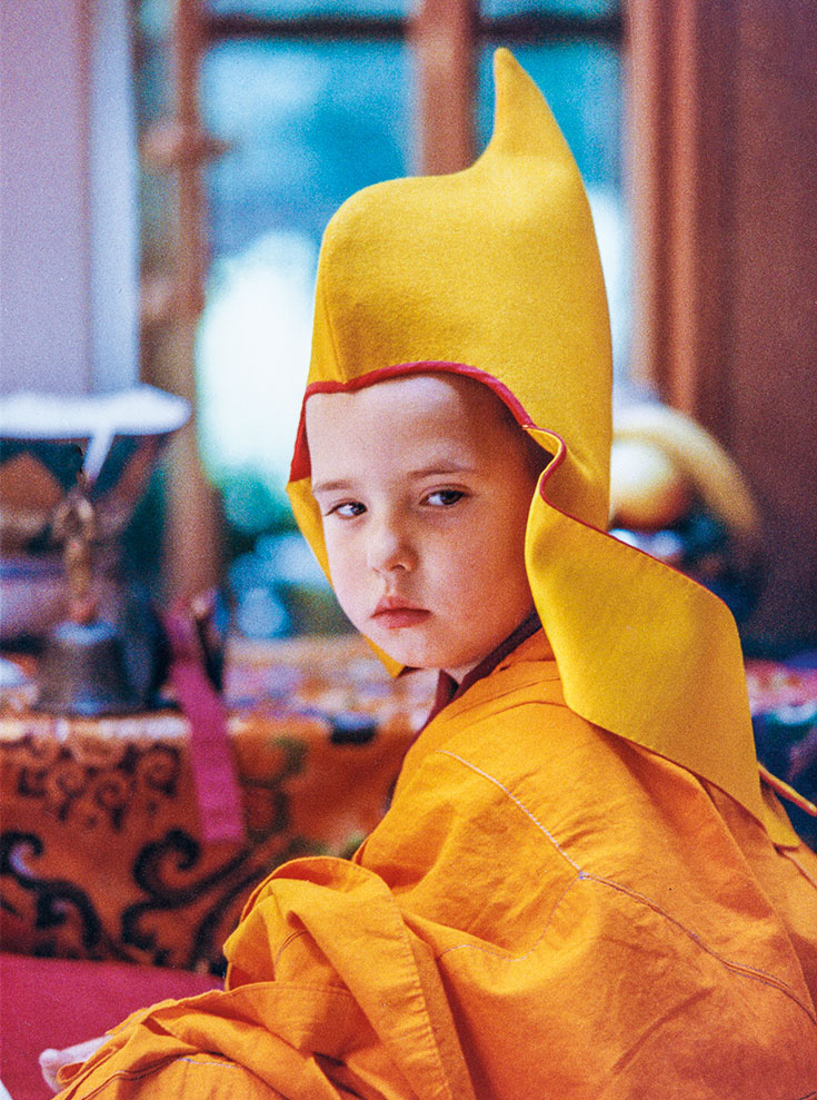 A young boy in yellow traditional robes and hat of a Tibetan Buddhist teacher.