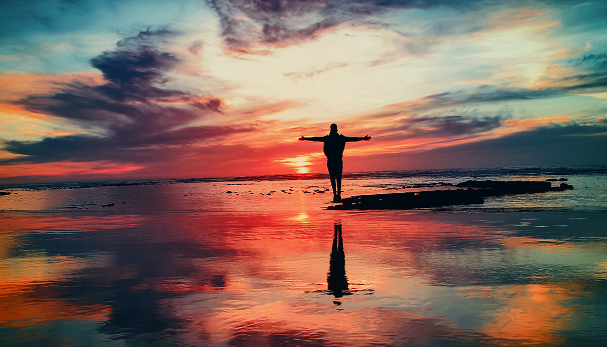 A man at sunset standing on the beach.
