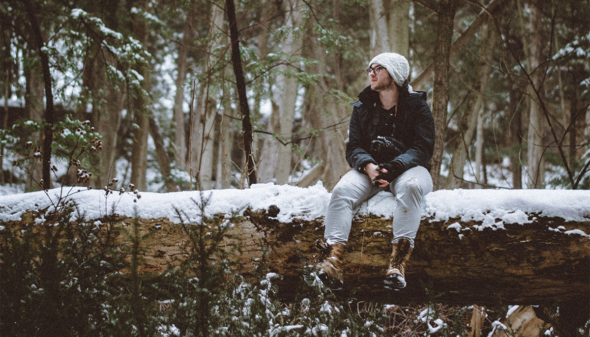 Man sitting on log in winter with camera