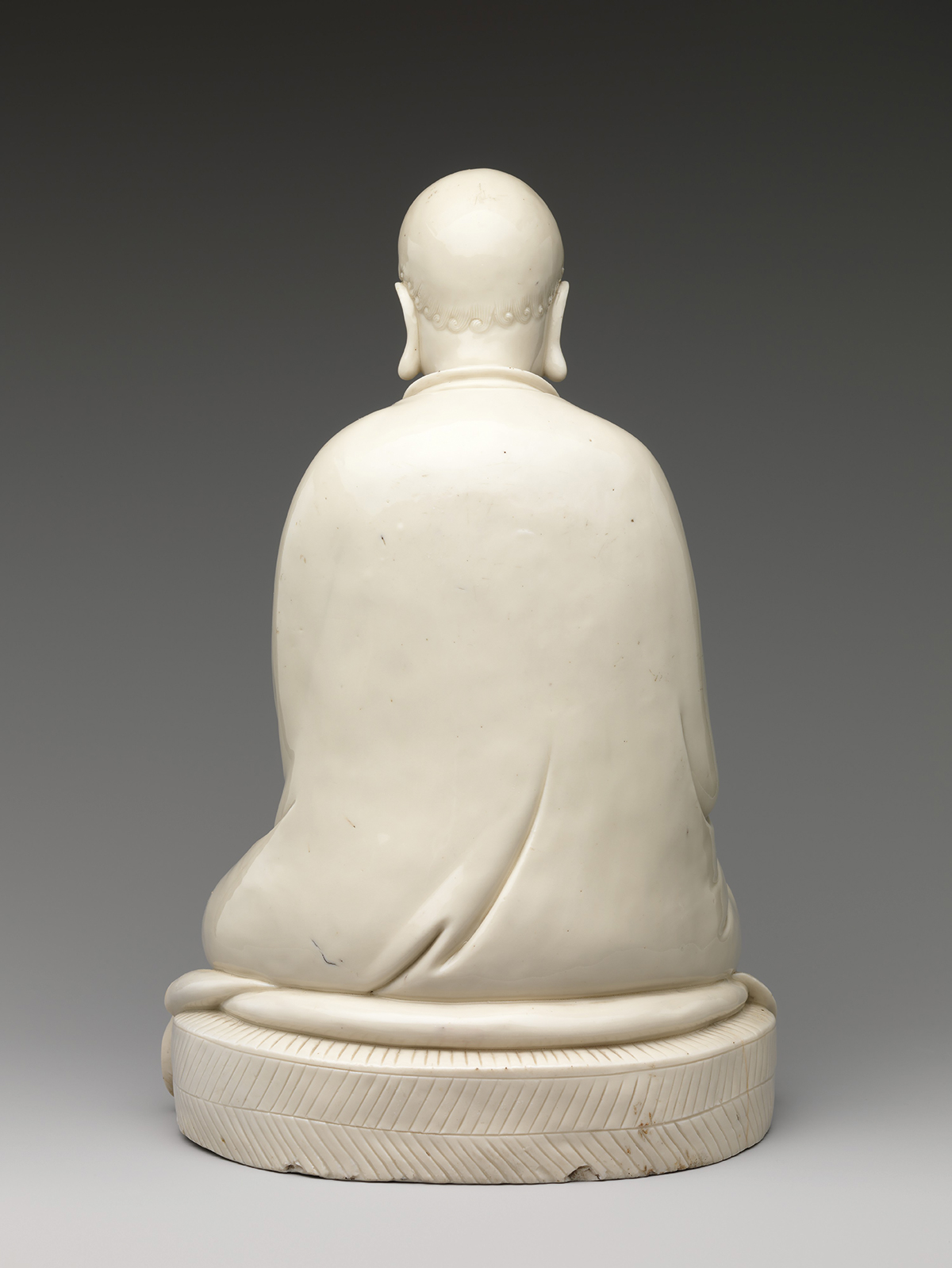 A marble Bodhidharma statue from behind.