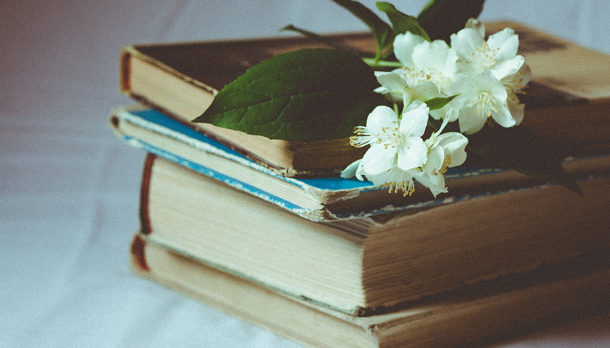 A pile of four aged books with flowers on top of the stack.