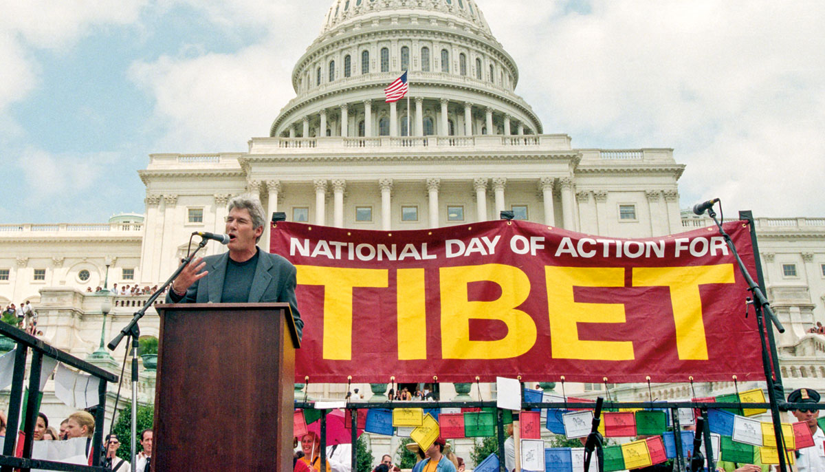"""A man stands at a microphone with a sign in the background that reads """"National day of action for Tibet."""""""