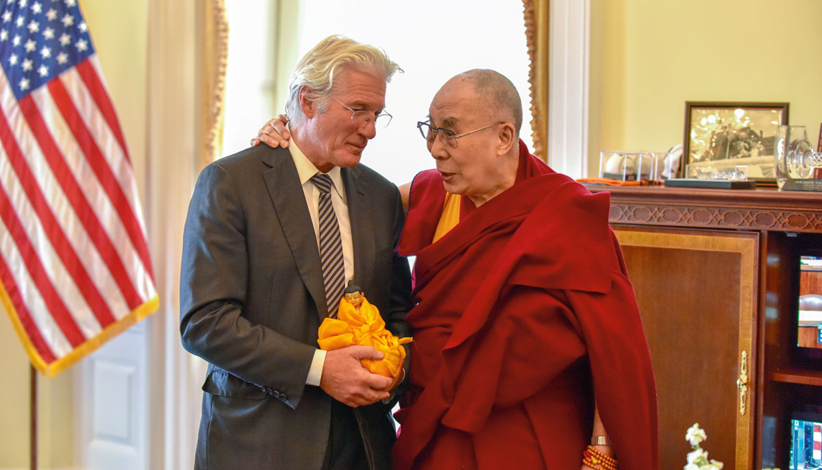A man dressed in a suit stands near the Dalai Lama, wearing red monk's robes.
