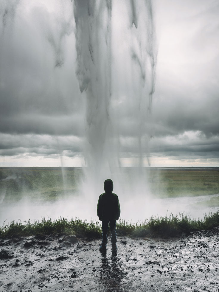 A young boy stands in front of a stream of water.
