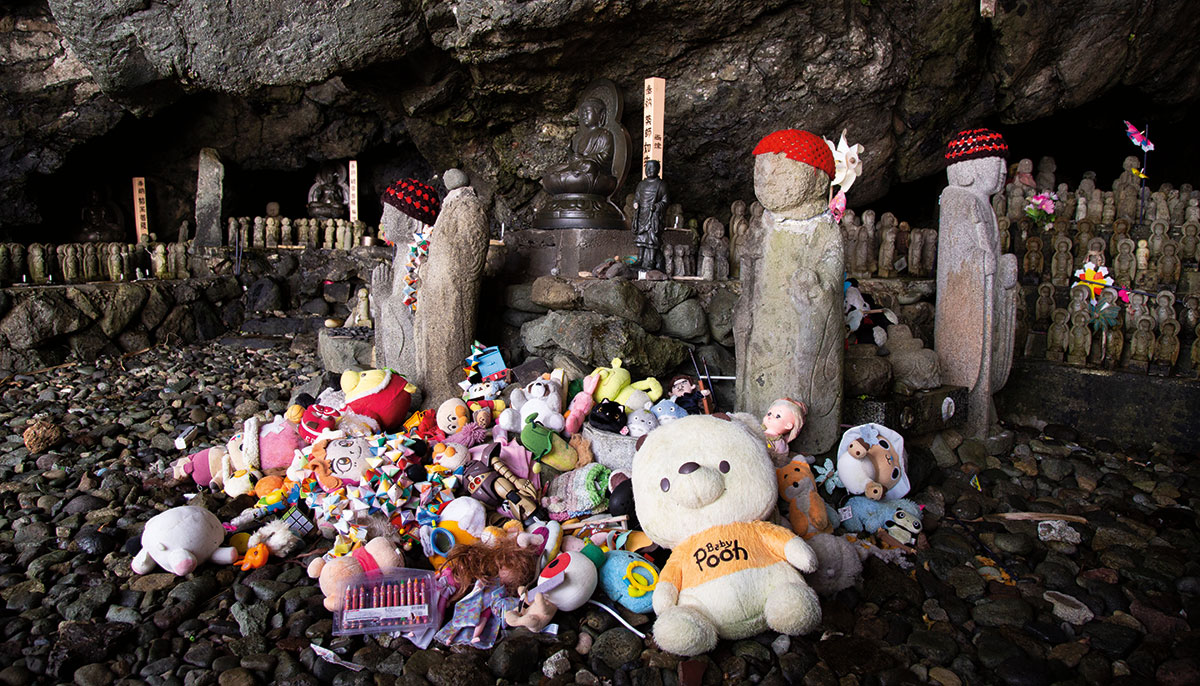 A picture of a bunch of toys in a pile inside of a cave. There are statues wearing red hats near the pile.