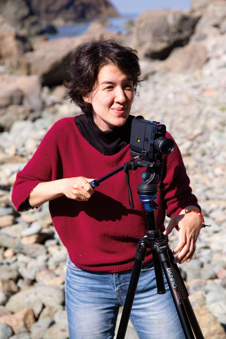 A woman wearing a red shirt and black pants on a beach. She is holding a camera.