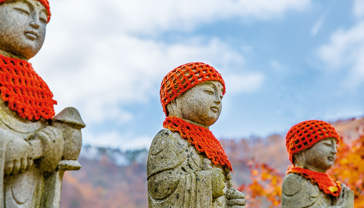 Statues wearing a crocheted red hat and bib.