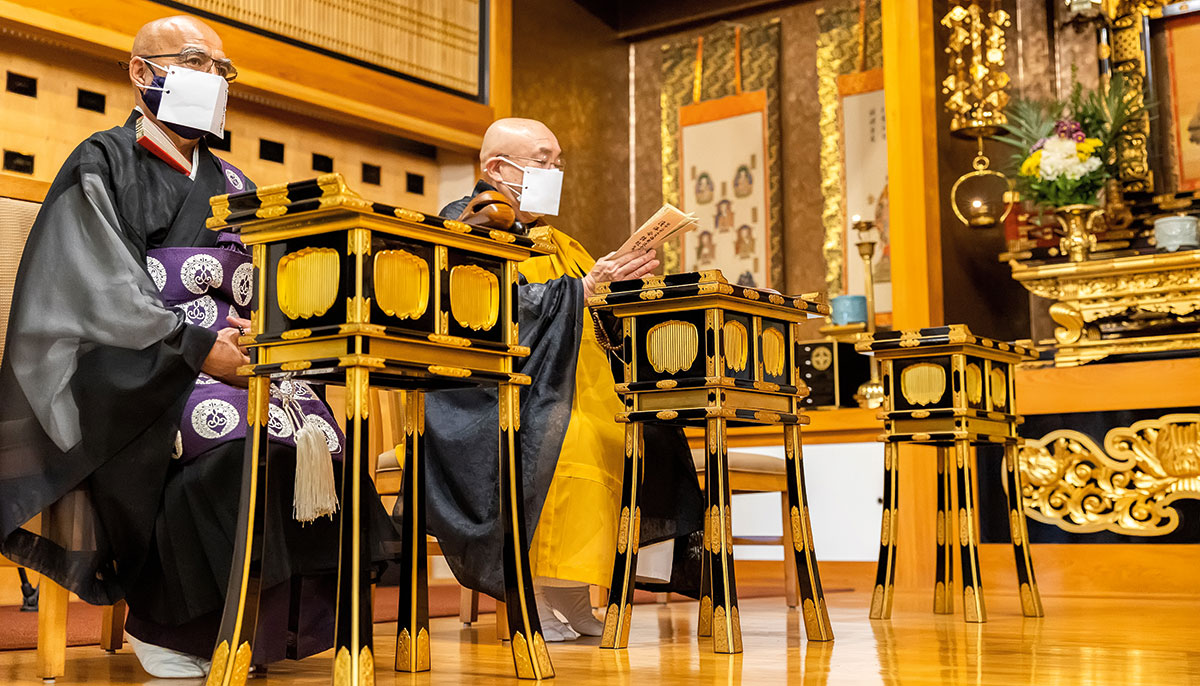 Two men in robes sitting in a gold room with masks on.