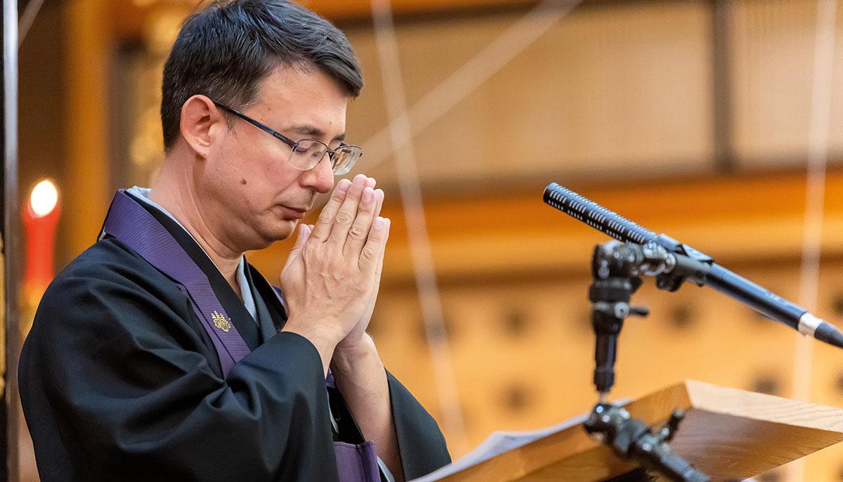A man with short hair and glasses with his hands in a praying motion at a microphone.