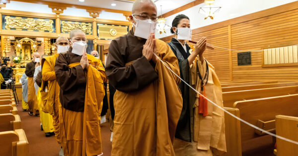 People in robes walking. Their hands are folded in a praying motion and they are all standing.