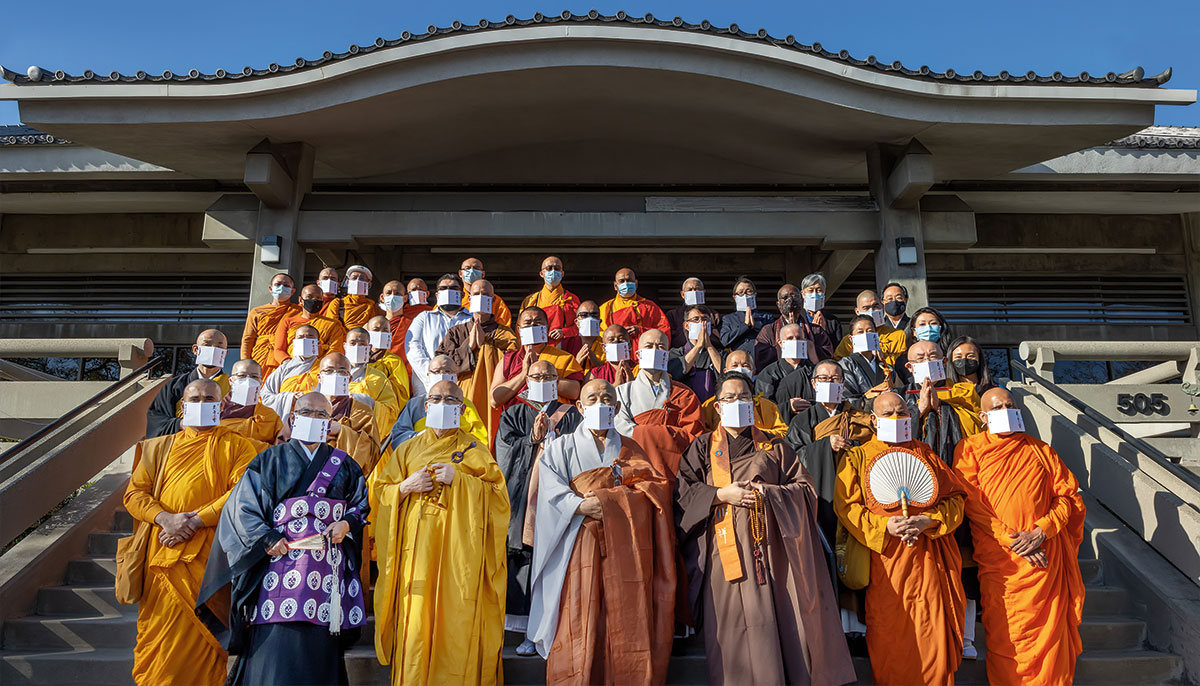 A group of people all wearing robes and masks posing together.